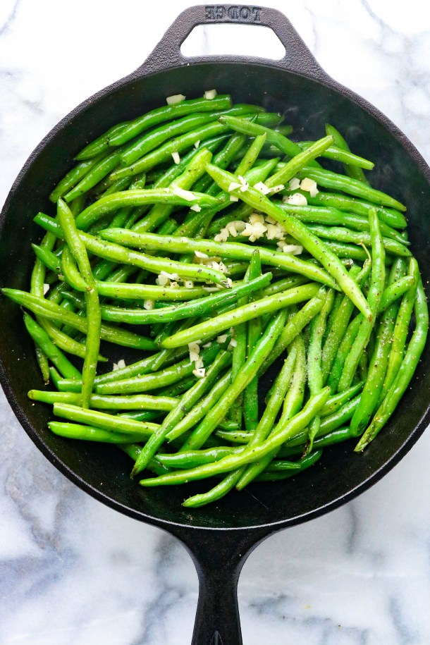 Cooking green beans in a pan with chopped garlic