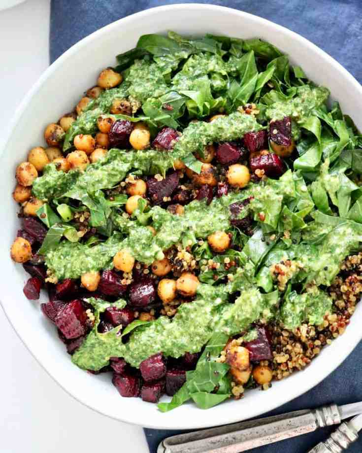 Perfectly roasted chickpeas and beets, mixed with hearty collard greens, fluffy quinoa and topped with lemony basil pesto. This is a bowl of goodness you will want to try today! #VEGANBUDDHABOWLS #CHICKPEAS #COLLARDGREENS #ROASTEDBEETS #ROASTEDCHICKPEAS #HOMEMADEPESTO