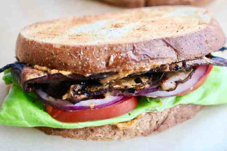Crispy smokey portobello mushroom bacon, crisp lettuce, tomato and onion and the most delicious cajun-spiced vegan mayo all stuffed between perfectly toasted rye bread. This vegan BLT is the BEST lunch or light dinner! #veganblt, #veganlunch, #portobello mushrooms