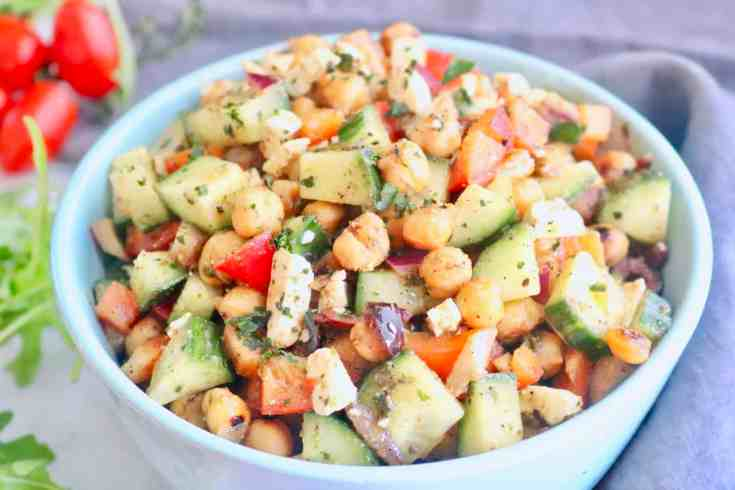 Seasoned roasted chickpeas, crisp cucumbers, red onion and bell peppers matched with salty, creamy feta cheese and all dressed with an herby homemade Italian dressing. Ready in 10 minutes! Vegetarian, gluten-free and a great meal-prep recipe! #mediterraneanchickpeasalad, #vegetariansalad, #chickpeas, #italliandressing, #fetacheese, #mealpreprecipe