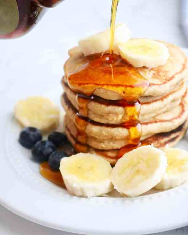 Pouring syrup onto healthy pancakes