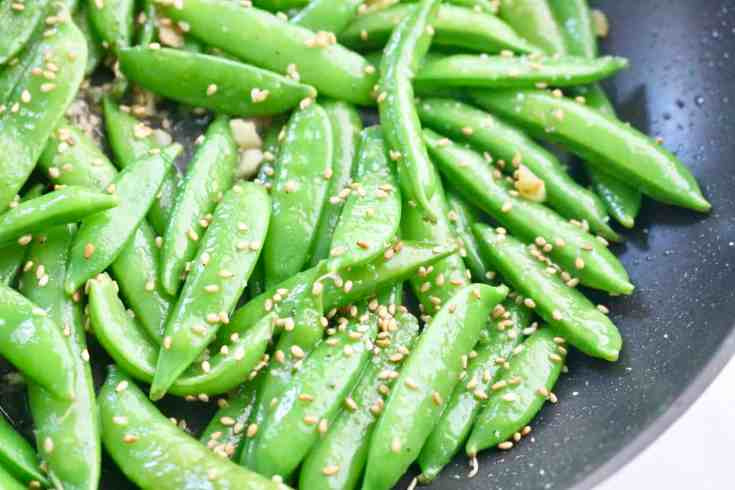 Sweet, crunchy sugar snap peas sautéed with sesame oil, fresh ginger and garlic and topped with toasted sesame seeds. Comes together in minutes, a great side dish or healthy snack! Vegan and Gluten-Free! #sugarsnappeas, #ginger, #garlic, #sesame seeds