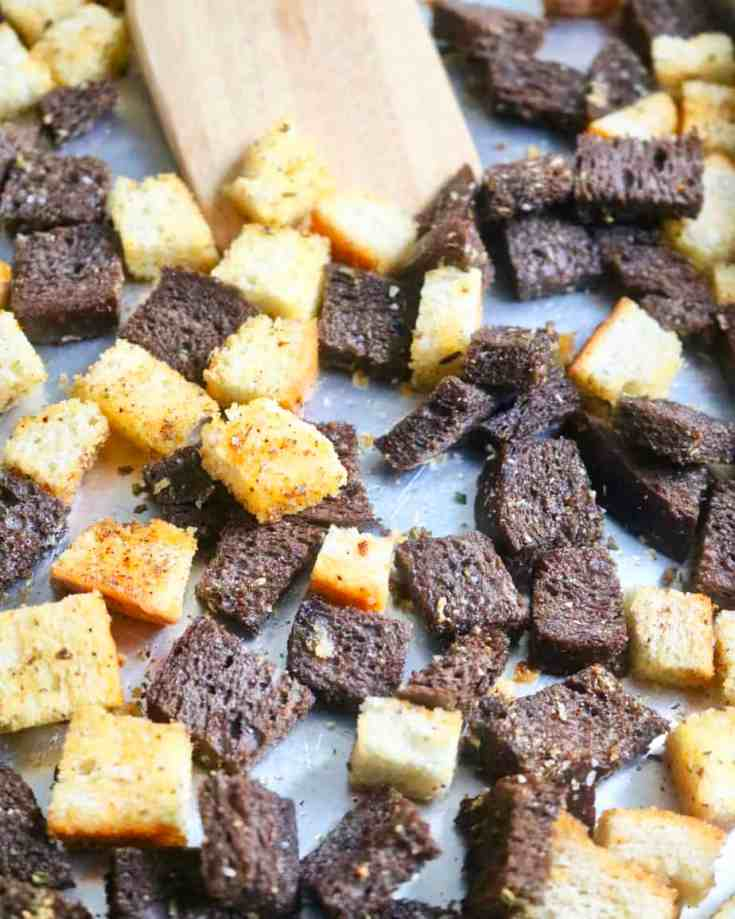 Homemade Croutons Recipe -Italian seasoned, crispy sourdough and pumpernickel bread cubed and baked into perfect little croutons that you can top on salads, soups or just enjoy as a snack! Ready in 20 minutes and these store in the fridge for up to 2 weeks! Super easy! #easyhomemadecroutons #howtomakecroutons #itallianseasonedcroutons #sourdoughbread #pumpernickelbread