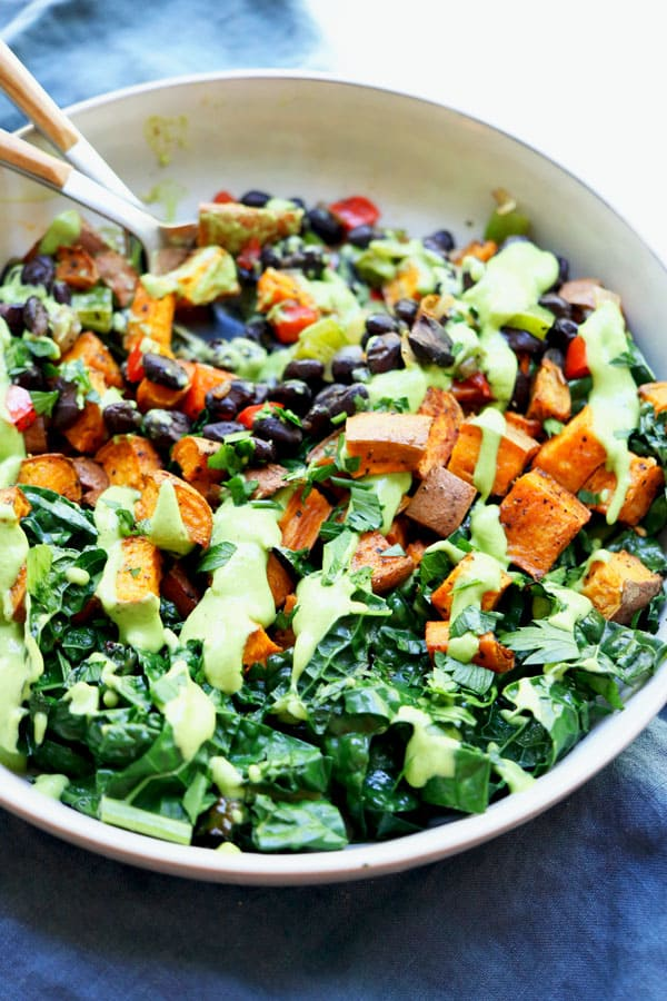 Perfectly seasoned, roasted sweet potatoes, garlicky sautéed kale, amazing cooked black beans with onions and peppers all piled into a bowl and topped with a creamy, tangy avocado sauce. A buddha bowl recipe that will blow your socks off and leave you feeling energetic and nourished all at the same time. Vegan and Gluten-Free! #sweetpotato #veganbuddhabowl #cookedblackbeans #perfectlysauteedkale #avocadocreamsauce