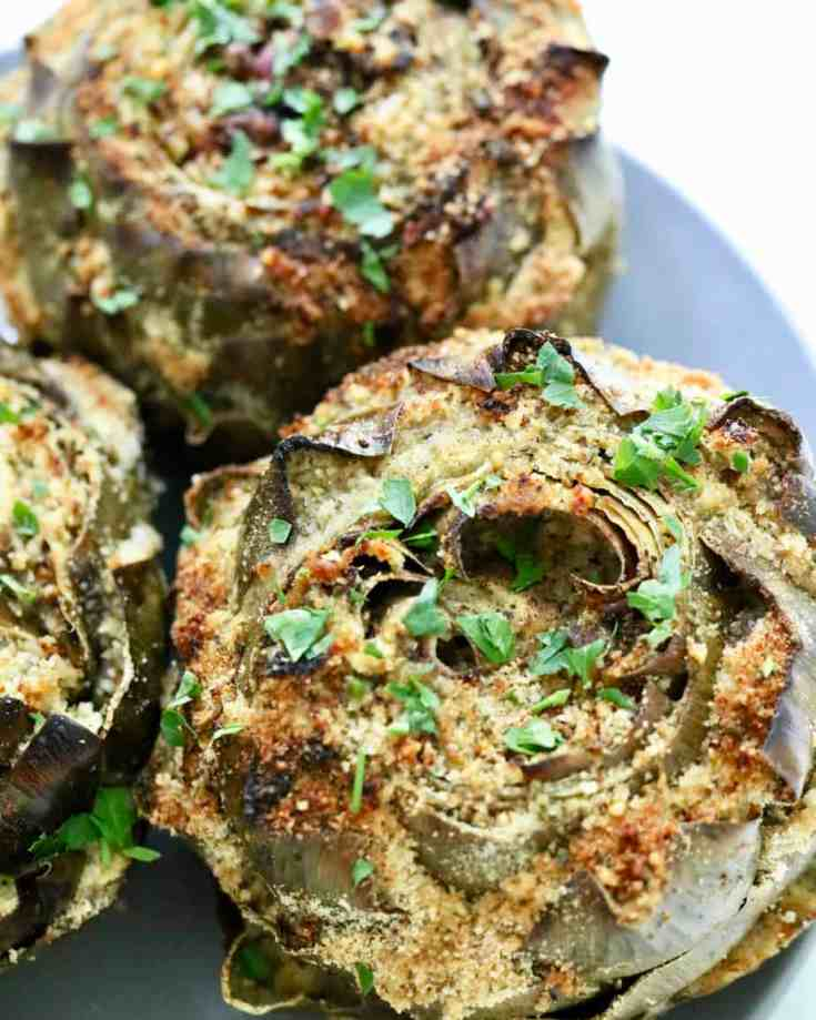 Simple, comforting and a crowd-pleasing recipe that you have to try! Hearty artichokes stuffed with a cheesy, crispy breadcrumb filling and drizzled with lemon juice and olive oil. Perfect for entertaining or impressing your family and friends! #italianstuffedartichokes #artichokes #healthyappetizers #breadcrumbfillin