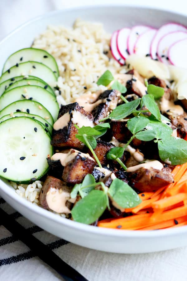 Sushi lovers will rejoice over this deconstructed sushi bowl. Better than take-out and it comes together in less than 20 minutes. It's also packed with plant based protein, vibrant veggies, soft cooked brown rice and topped with spicy mayo, sesame seeds and crisp watercress. Vegan and Gluten-Free! #vegansushi bowl #buddhabowls #crispytofurecipes