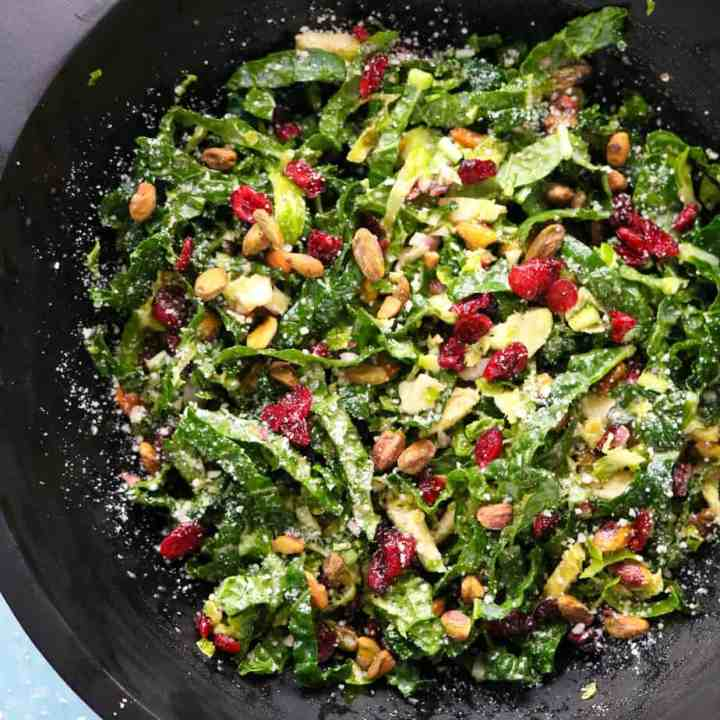 Shredded-brussel-sprout-and-kale-salad-in-a-black-salad-bowl-on-top-of-a-yellow-linen_