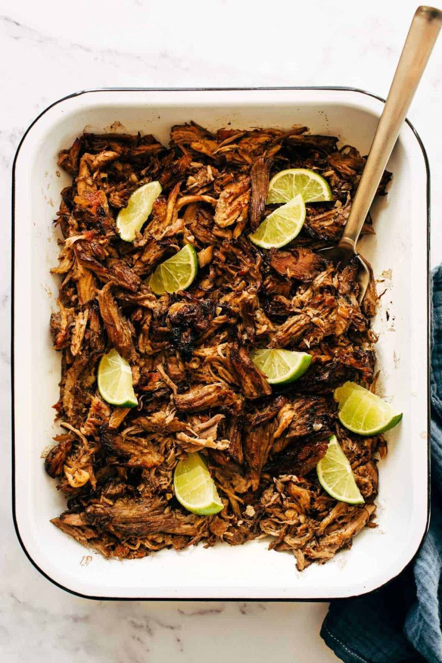 Carnitas in a pan with limes and a serving fork.