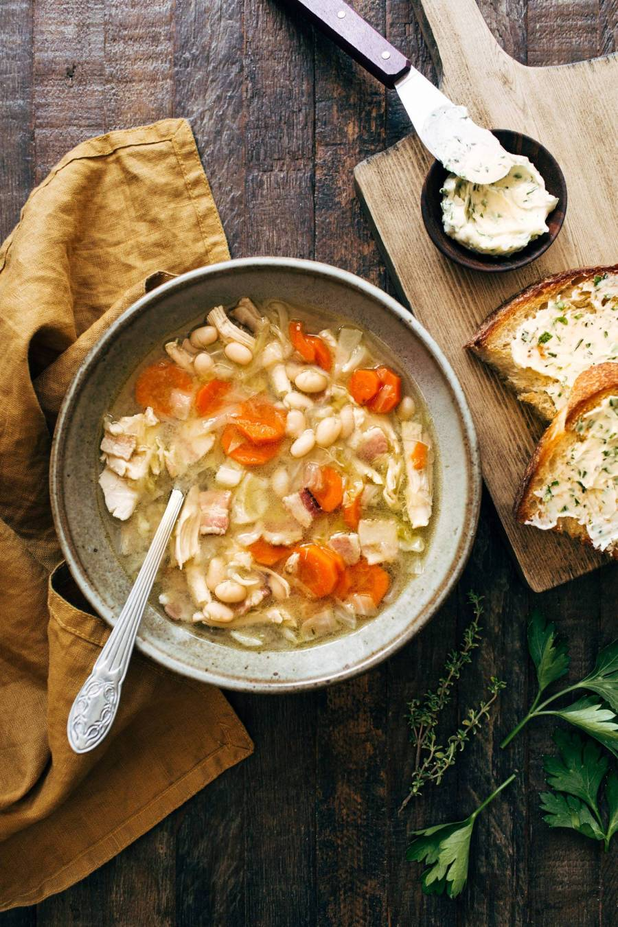 Chicken stew in a bowl with a spoon and bread on the side.
