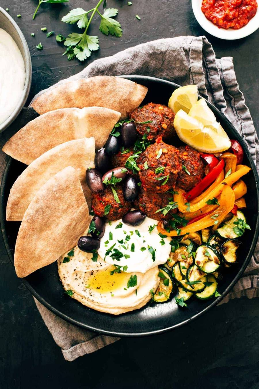 Harissa Meatballs with Whipped Feta in a bowl with peppers, zucchini, and pita bread