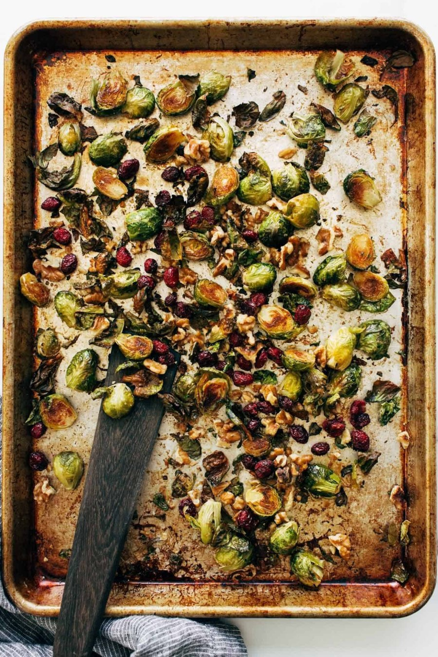Roasted Brussels sprouts on a pan with a spatula