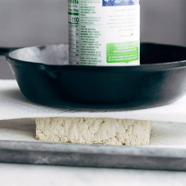 Pressing water out of tofu.