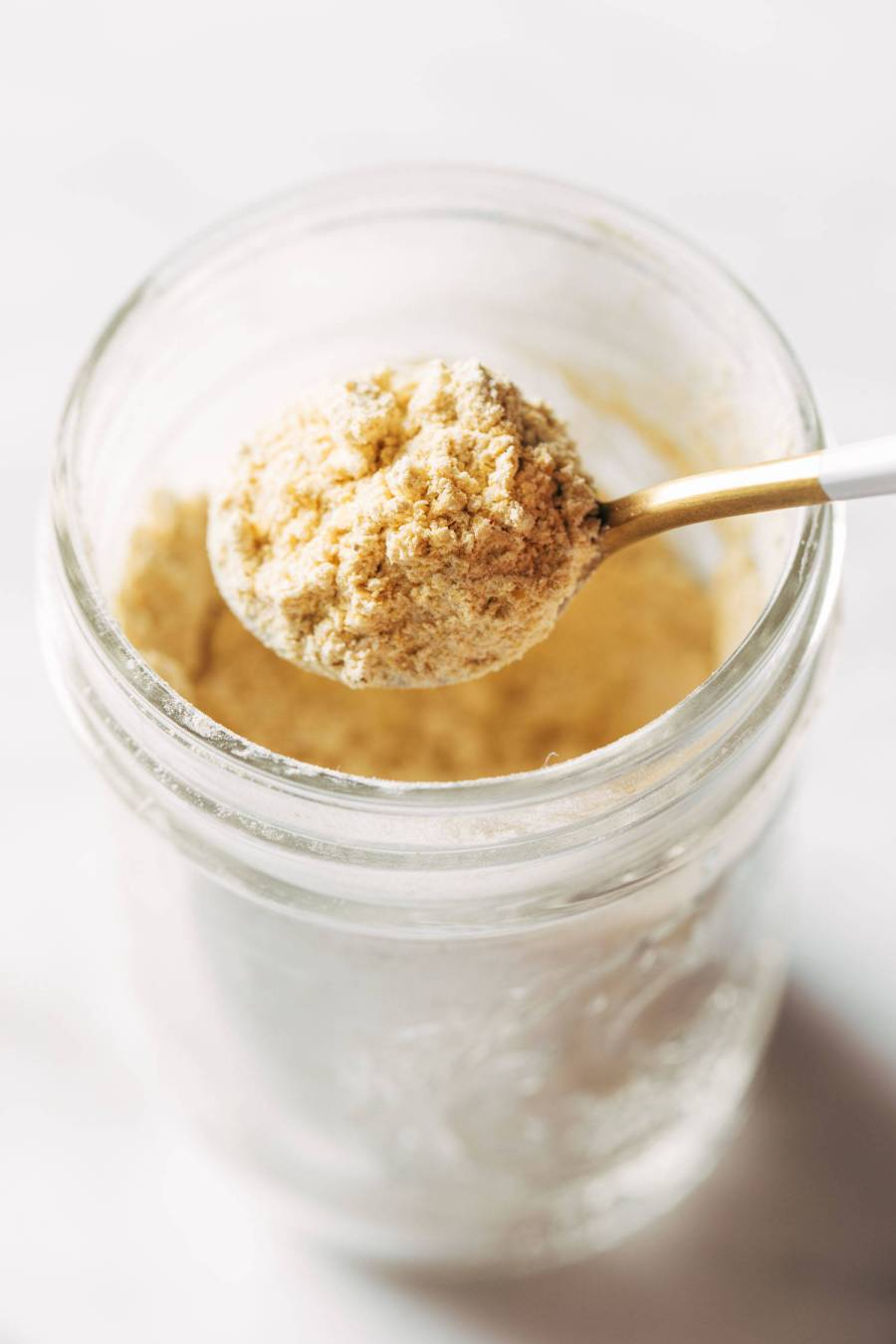 Vegan cheese powder being scooped with a spoon.