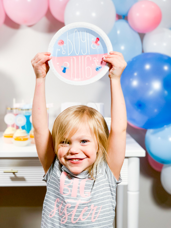 Big Sister holding Gender Reveal Plates - Gender Reveal Party Ideas by Pineapple Paper Co.