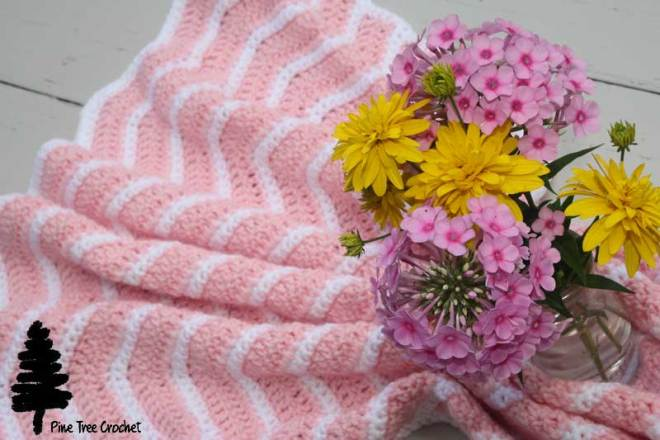 pink crocheted blanket with pink and yellos flowers in the vase