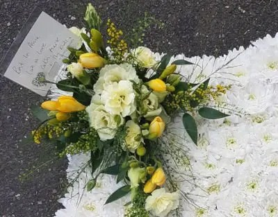 Sympathy flowers white cushion of flowers with yellow spray of flowers and message card