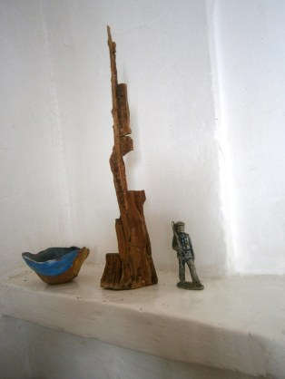 Lead soldier, wooden shard and clay pinch pot