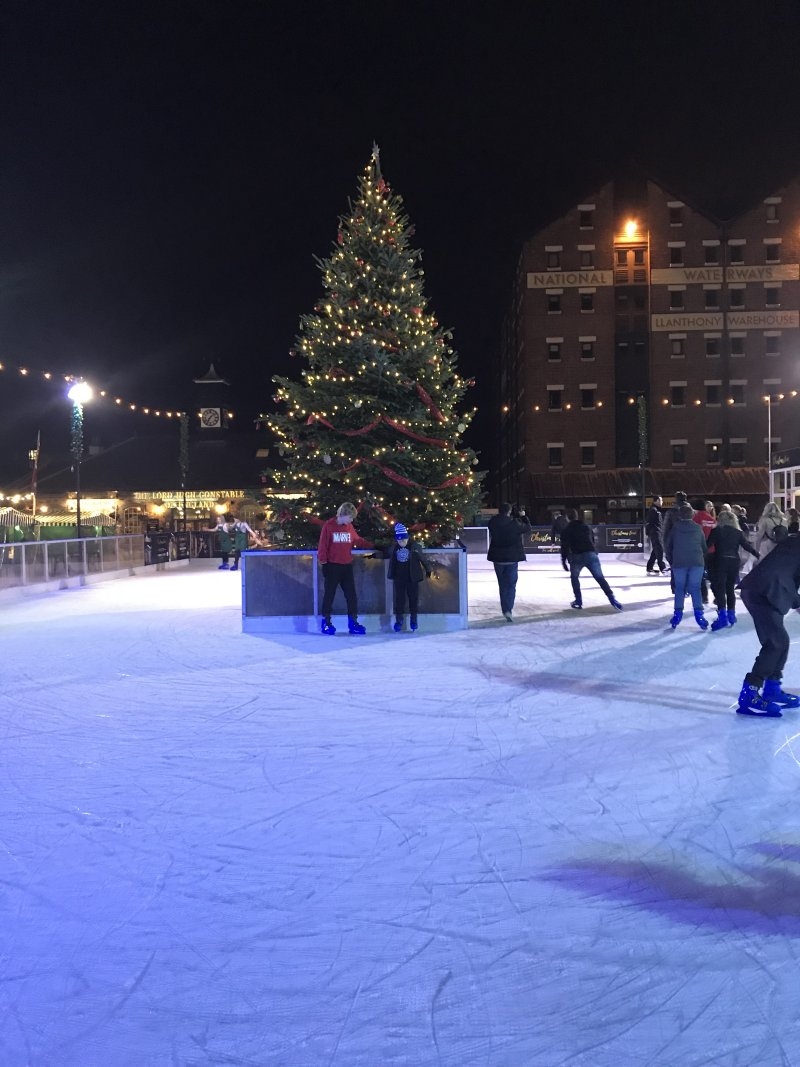 people ice skating with a christmas tree in the middle of the rink and two boys helping one another