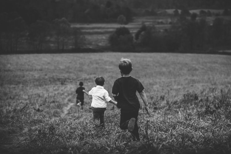 3children playfully running across a field