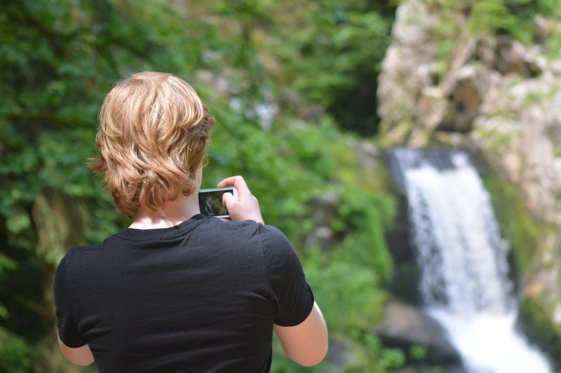 teen taking picture of waterfall in black forest