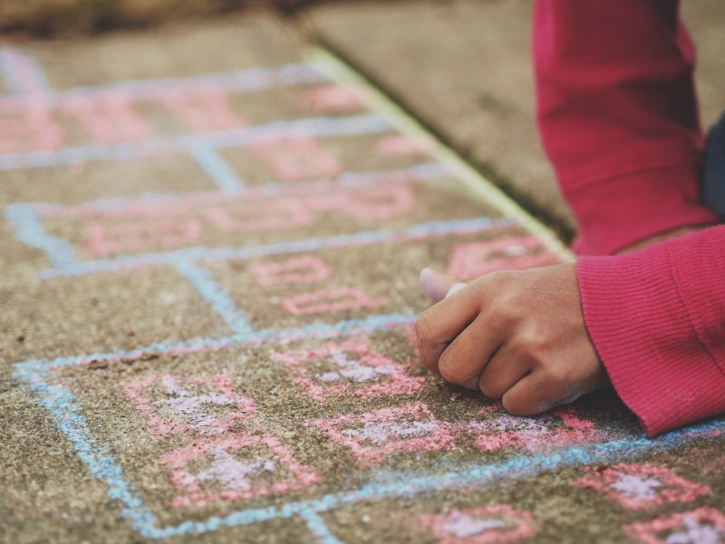 child with chalk drawn on the pavement
