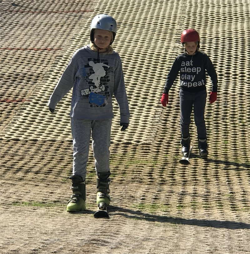 two boys on dry nursery ski slopes