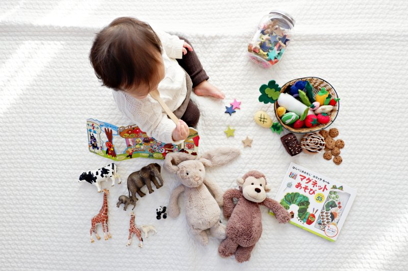 young child sat surrounded by toys