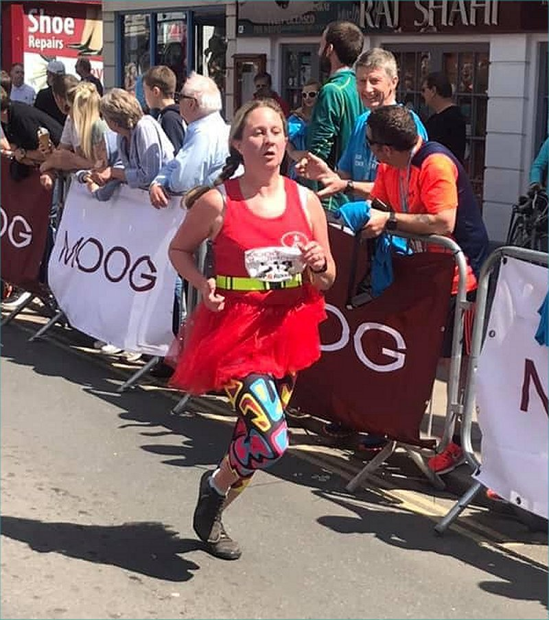 woman running to the finish line wearing a tutu