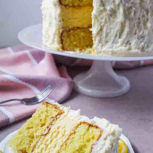 side shot of lemon cheesecake layer cake on cake stand