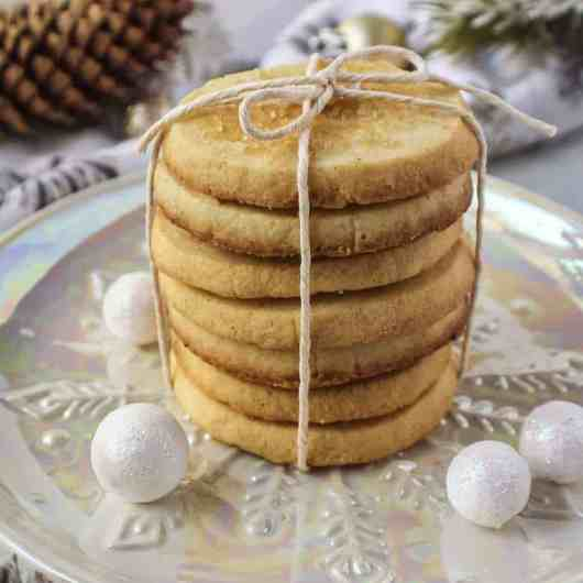 cardamom butter cookies tied in kitchen twine on top served on a small white plate with pine cones in shot