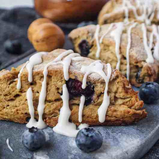 vegan blueberry scones with a powdered sugar glaze on a marble serving dish