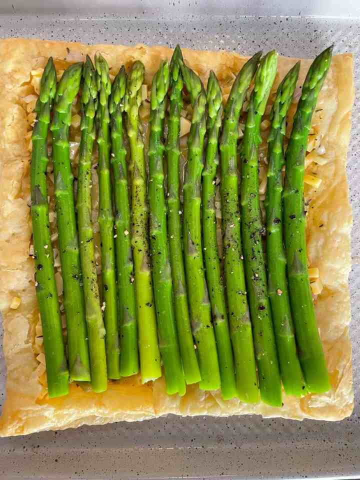 overhead shot of unbaked asparagus tart on parchment.