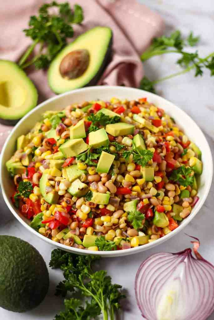 side angle shot of avocado and black-eyed pea succotash in white bowl