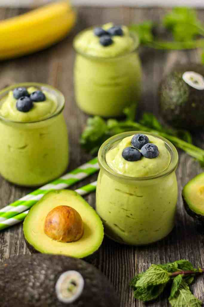 side shot of tropical avocado smoothies with fresh avocados in perimeter of shot
