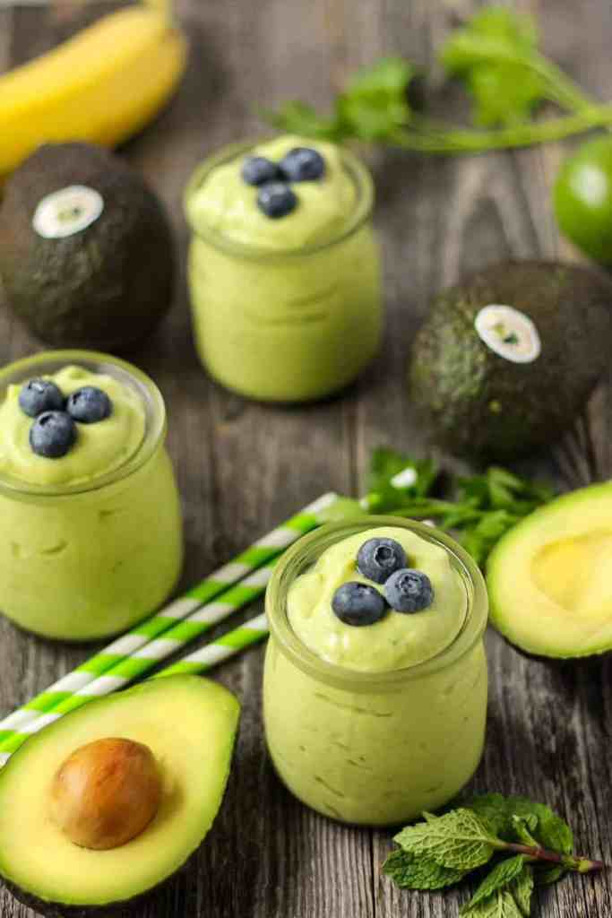 side shot of tropical avocado smoothies on wooden surface with fresh avocados in perimeter of shot