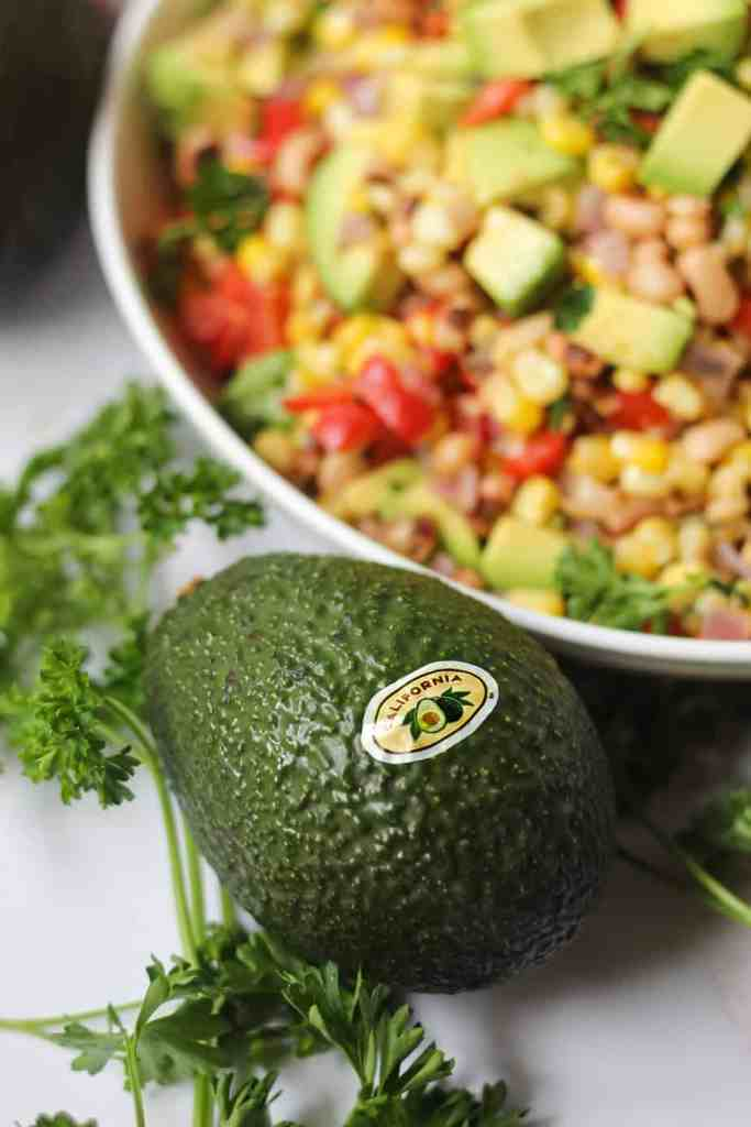 close up of avocado with succotash in the background