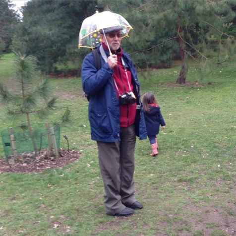 Dad under a kid's umbrella