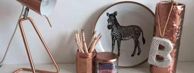 Copper lamp, pencil pot and vase, and zebra plate on a white desk