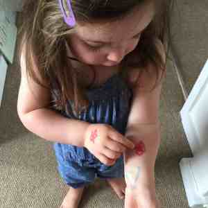 Toddler with felt tip on her arm