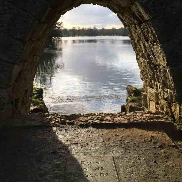 Looking through an arch at a lake at Stowe Landsacpe Gardens
