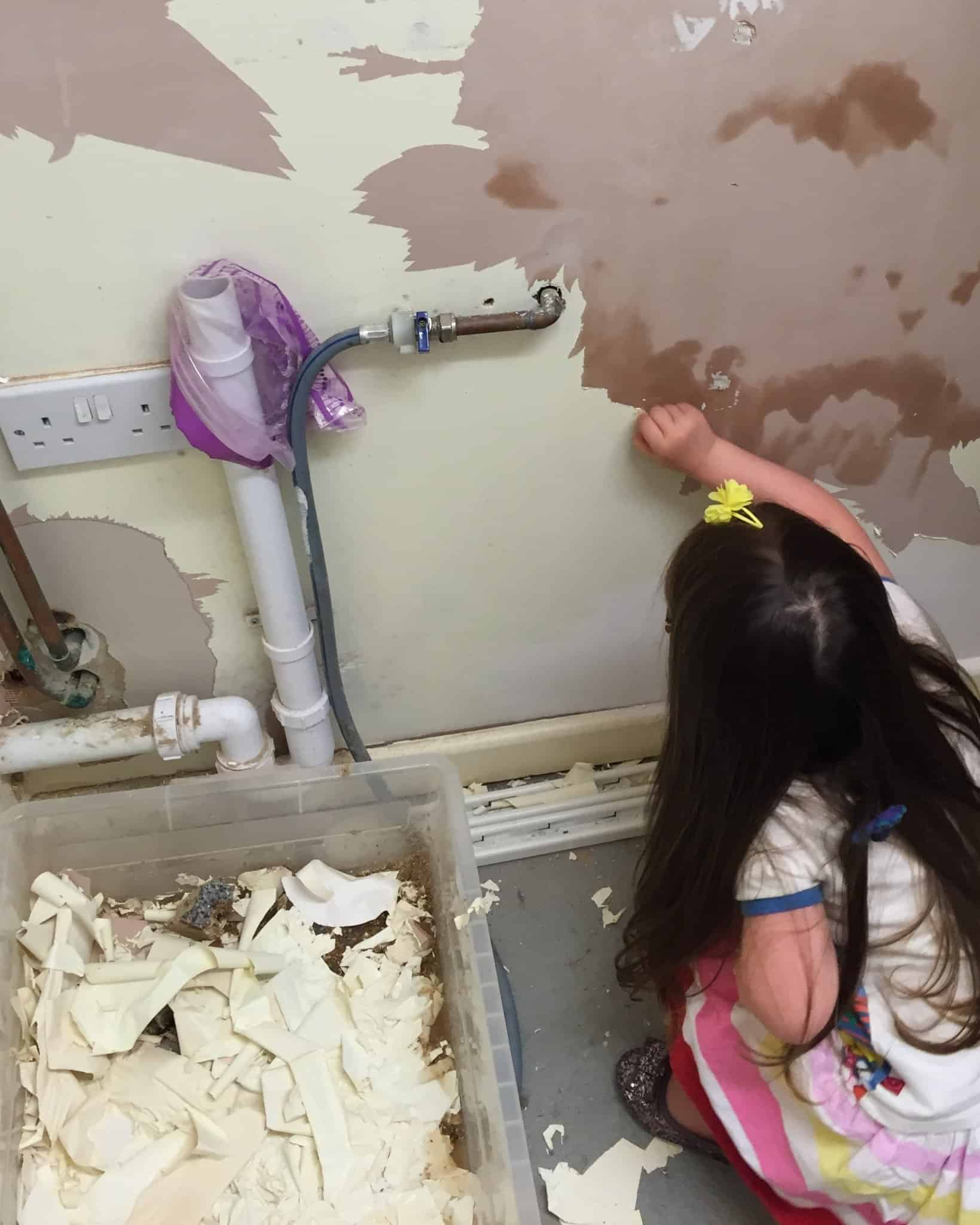 Thea peeling old paint off the utility room wall