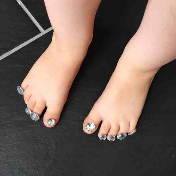 Thea's feet with jewel stickers over her toenails