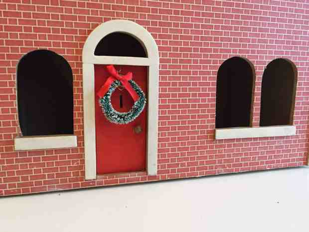 Dolls house with Christmas wreath on a red front door