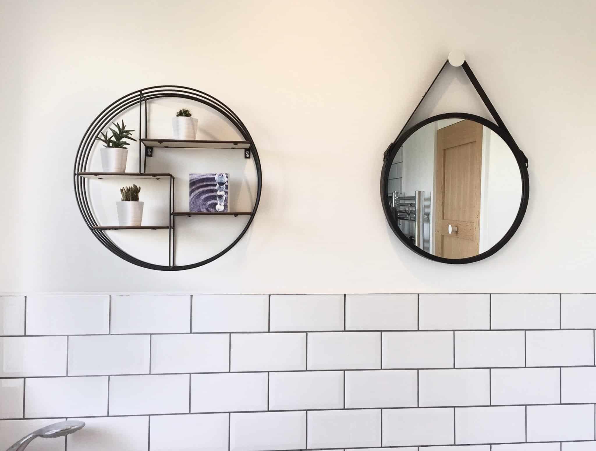 Black circular shelving and mirror in a monochrome family bathroom
