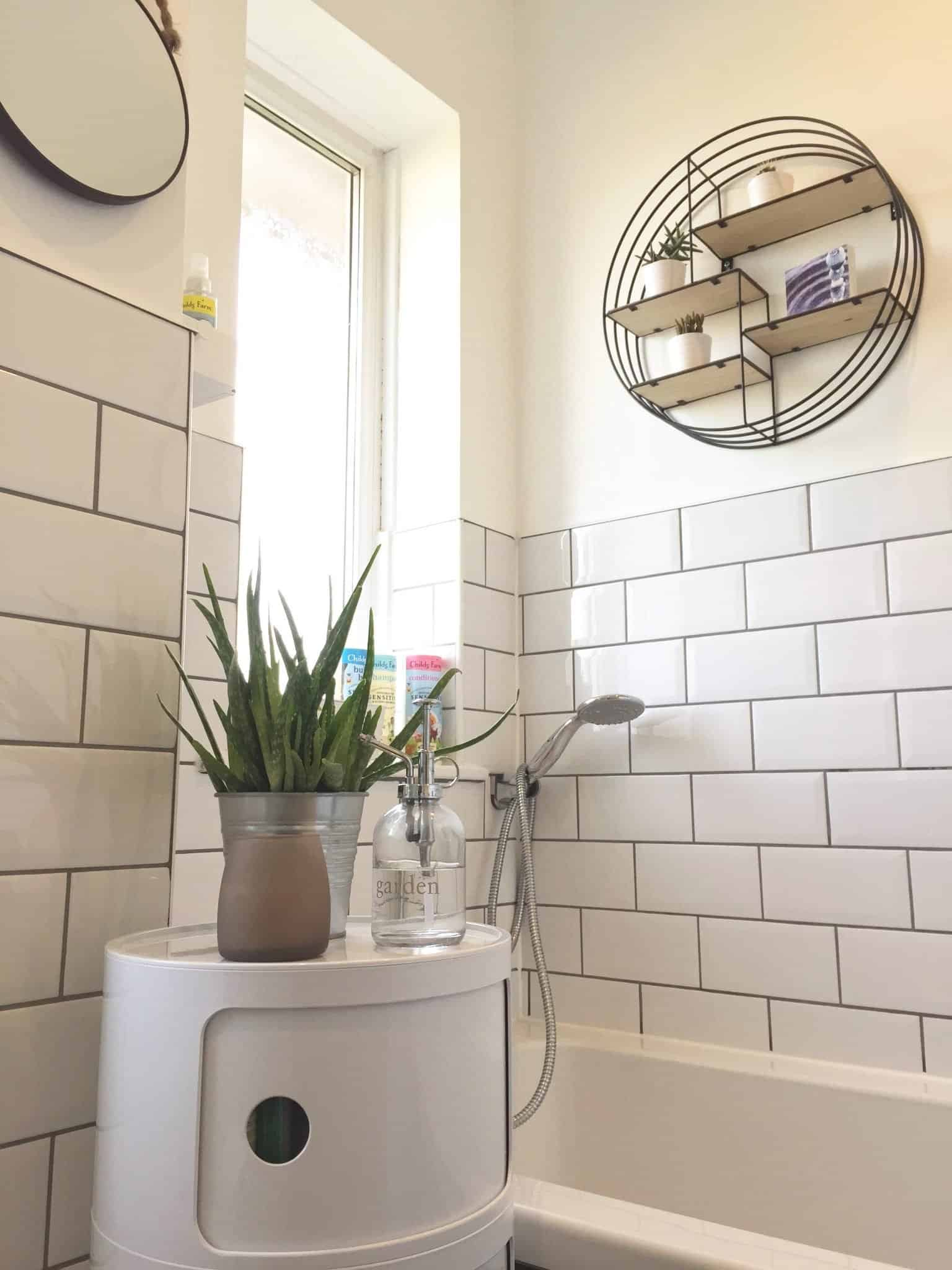White bathroom with white metro tiles and grey grout and circular storage unit