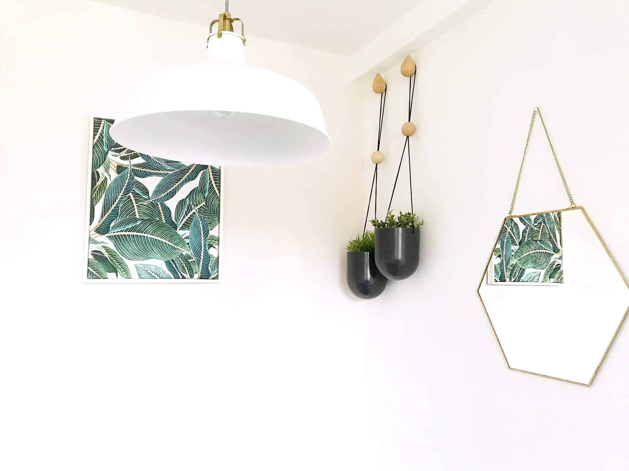White room with green tropical plant prin reflected in a hexagonal mirror