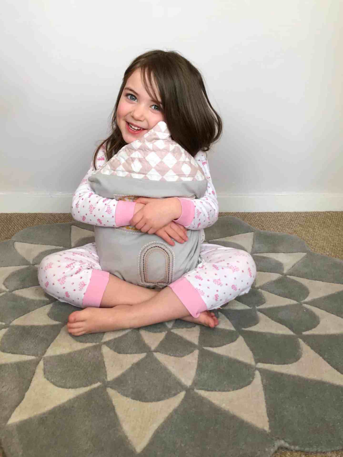 Cuddling a house cushion on a grey patterned rug