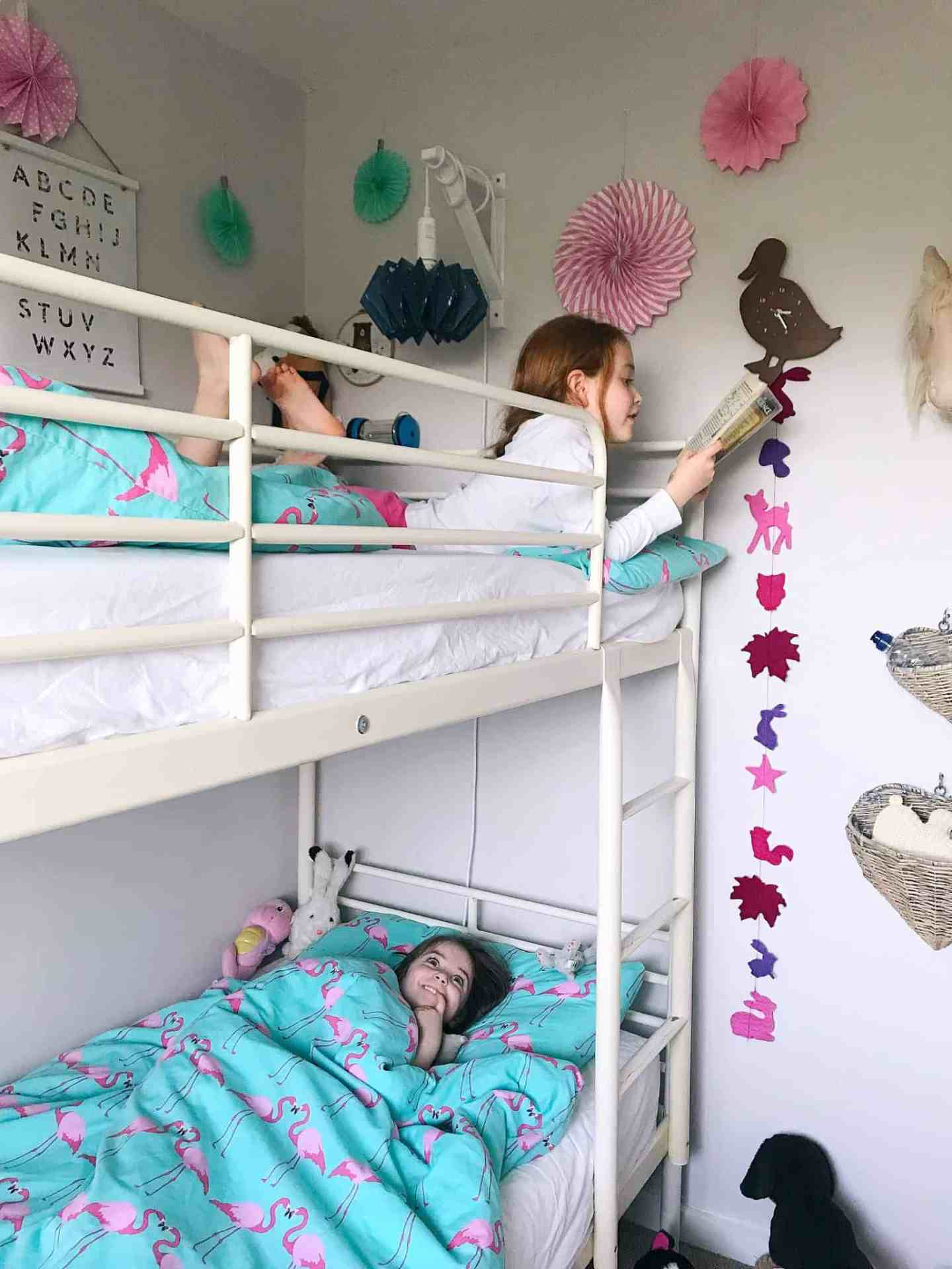 Sisters reading in their shared bedroom with bunk beds