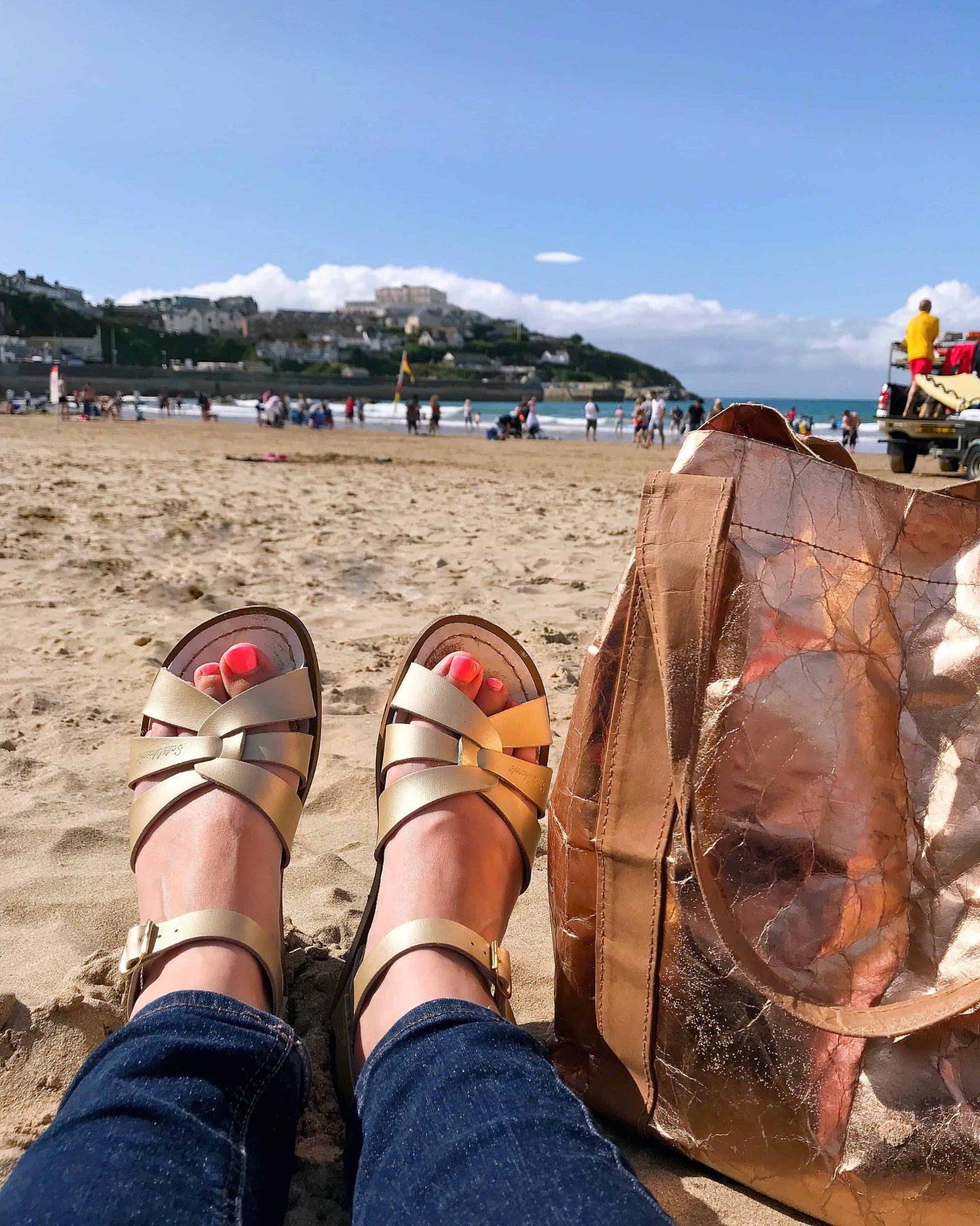 Relaxing on the beach at Newquay with gold Saltwater Sandals