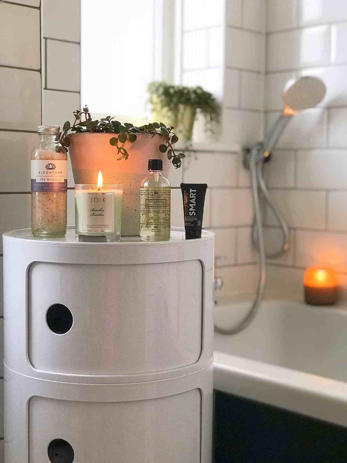 Scented candles and natural beauty products in a monochrome bathroom
